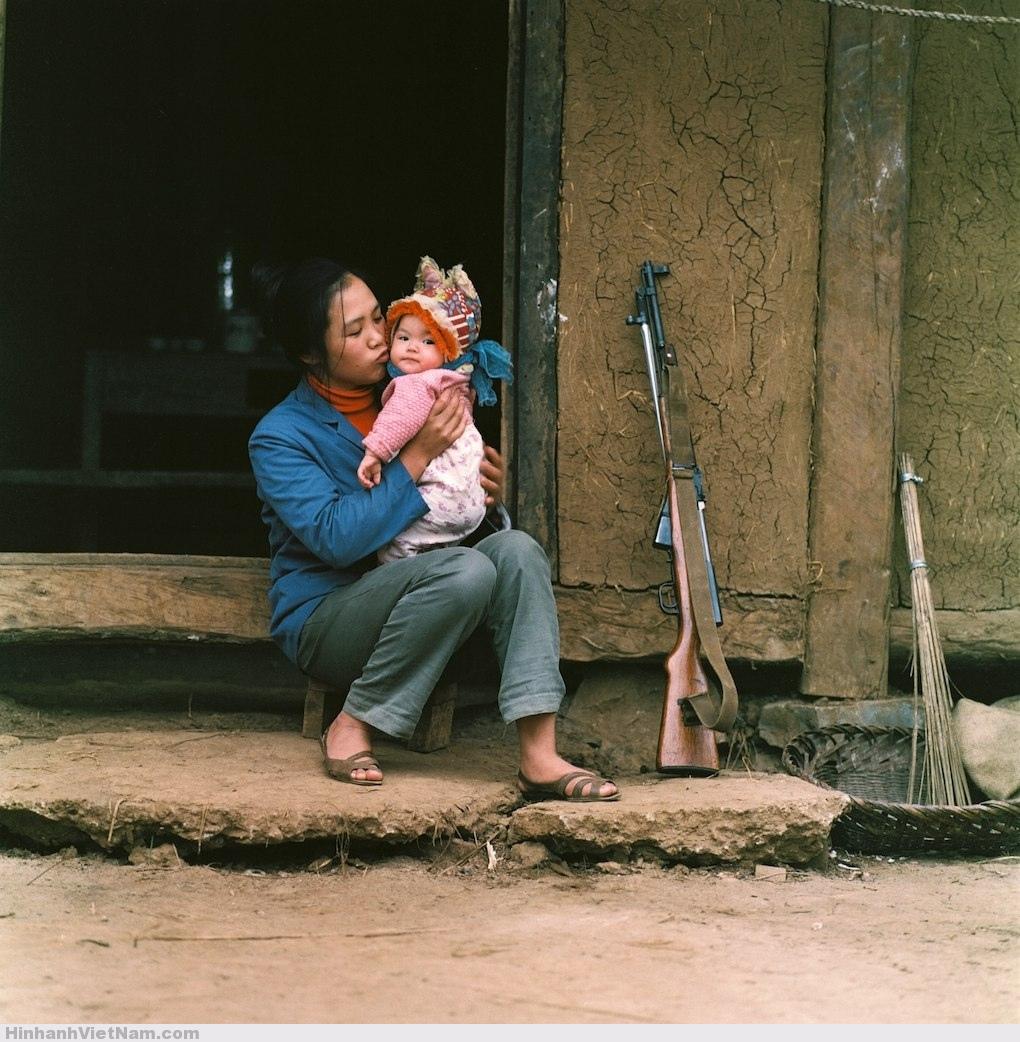 Nữ dân quân nựng yêu con nhỏ