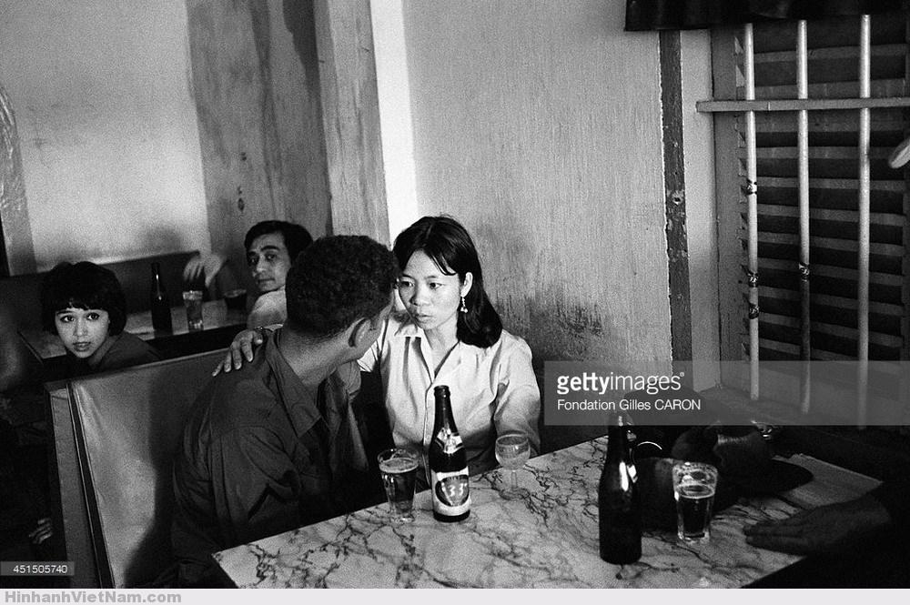 """Những cuộc tình chớp nhoáng của lính Mỹ thường bắt đầu tại các quán bar. Sau màn """"làm quen"""" bằng bia rượu, họ sẽ đưa các cô gái Việt về khách sạn hoặc về nhà trọ... Ảnh: Gilles Caron."""