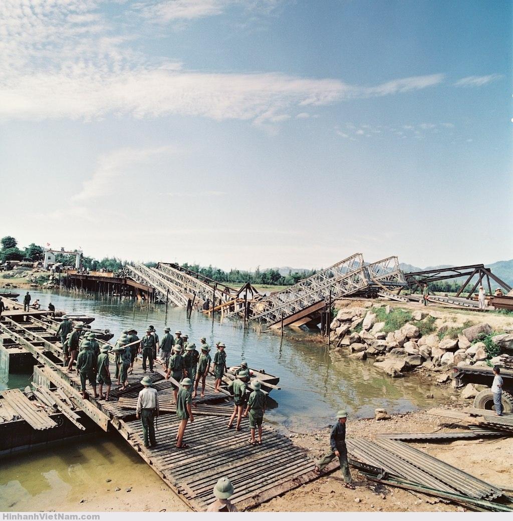 Một cầu tạm đang được dựng cạnh một cây cầu bị bom Mỹ đánh sập