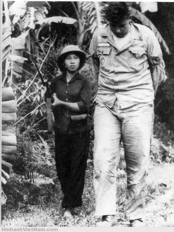 """Bức ảnh chụp """"O du kích nhỏ"""" Nguyễn Thị Kim Lai áp giải một phi công Mỹ bị bắt vào năm 1965. Hình ảnh một nữ dân quân nhỏ bé áp giải viên phi công cao lớn đã trở thành biểu tượng hào hùng của cuộc kháng chiến chống Mỹ, giữa một dân tộc nhỏ bé với kẻ thù lớn hơn gấp nhiều lần"""