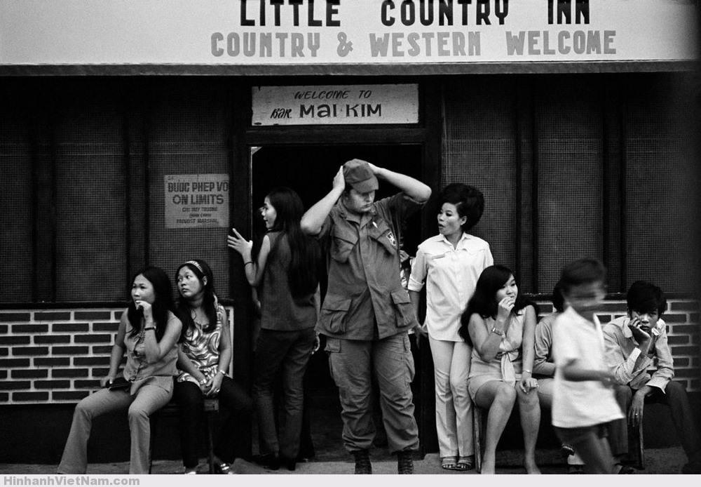 Bên ngoài quán bar Mai Kim ở Cần Thơ, 1970. Phía sau các quán bar phục vụ lính Mỹ là sự bảo kê từ giới chức quân đội Sài Gòn. Ảnh: Philip Jones Griffiths