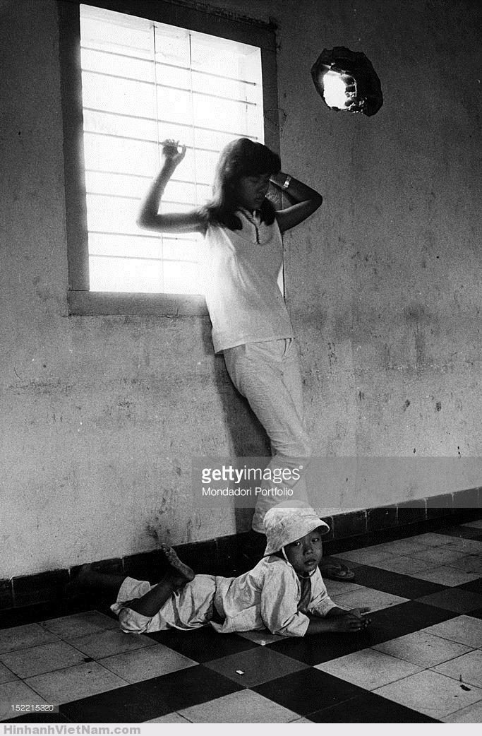 Một cô gái bán dâm cùng đứa con tại địa điểm hành nghề là một khu nhà lỗ chỗ vết thủng do bom đạn, Sài Gòn tháng 1/1968. Ảnh: Mondatori.